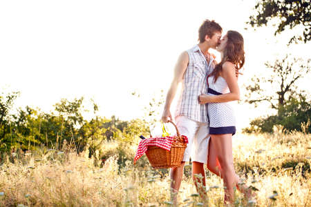 Young romantic couple kissing on their way to a picnic  photo