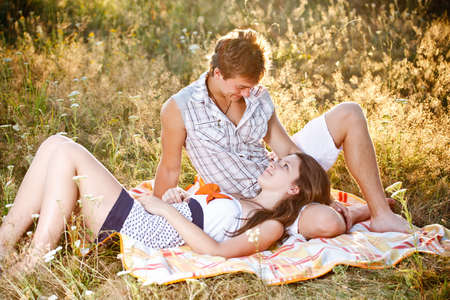 Young couple in meadow relaxing photo