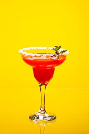 Watermelon martini drink with mint on yellow background
