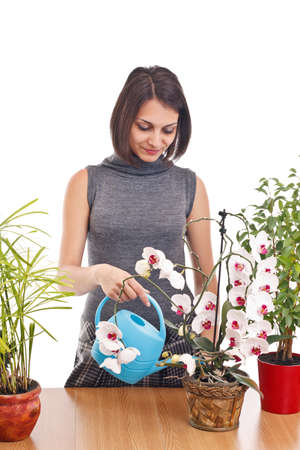 Cheerful girl watering flowers, studio shot photo