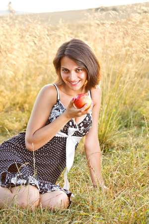 Beautiful young woman with apple at meadow Stock Photo - 14746126