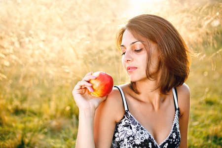 Beautiful young woman with apple at meadow  Stock Photo - 14745189