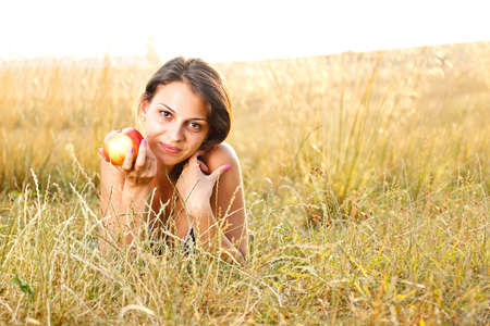 Portrait of a beautiful woman lying in a meadow in summer and eating apple Stock Photo - 14746094