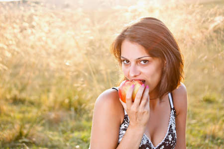 Beautiful young woman with apple at meadow Stock Photo - 14742374