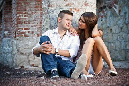 boyfriend: Pareja joven sentado junto a la pared de ladrillo