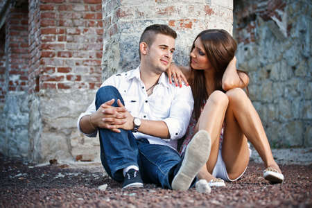 Young couple sitting by brick wall