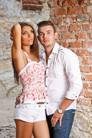 Young couple against a brick wall.  photo