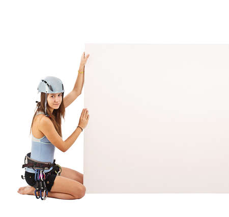 Woman in climbing equipment holding a blank cardboard isolated in white  photo