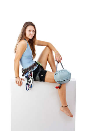 Young woman in climbing equipment sitting a blank banner isolated in white  photo