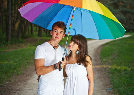 Teenage couple under an umbrella outside  photo