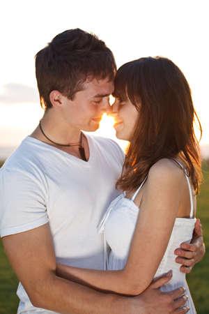 intymno: Atrakcyjna młoda para romansuje w parku przy zachodzie słońca. Zdjęcie Seryjne