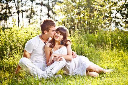 Portrait of romantic teenage couple sitting in park
