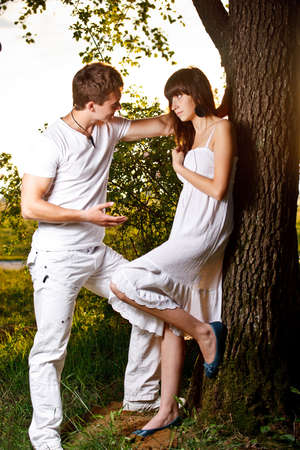Teenage couple by tree in park  photo