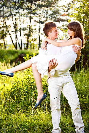 carrying girlfriend: Happy young man carrying girlfriend in his arms