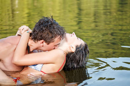 seduce: Young beautiful couple are kissing in the water