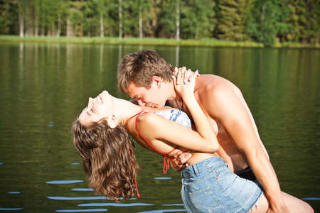 Young couple kissing in a montain lake  photo