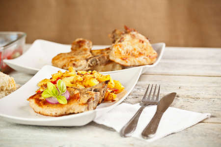 loin chops: Grilled pork loin chops served with potato Stock Photo