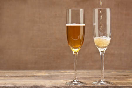 Champagne pouring in glass on grungy wood table Stock Photo - 15348179