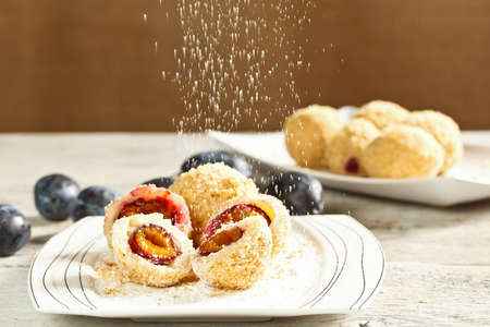Plum dumplings with buttered breadcrumbs and sugar photo