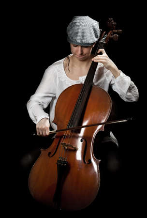 girl playing cello, in black background Stock Photo