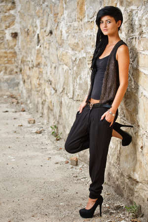 adult wall: Beautiful woman standing by a stone wall