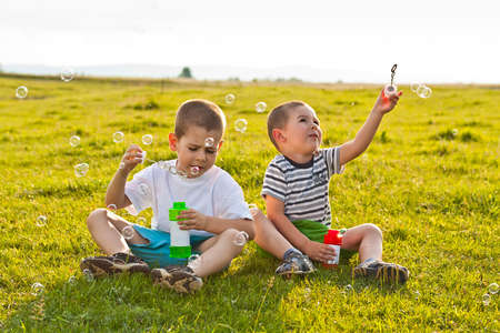 Boys sitting on green grass and blowing soap bubbles  photo