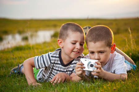 Brothers lying on meadow and taking pic on their camera Stock Photo - 15375649
