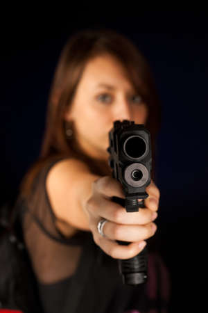 Sexy young woman with a gun isolated on black Stock Photo - 15348419