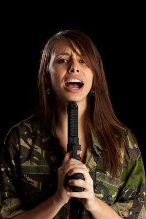 lanzamiento de bala: Mujer con un arma en la mano aisladas sobre fondo negro