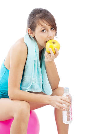 Sport fitness woman on exercise pilates ball eating an apple relaxing taking a break. Stock Photo - 15348535