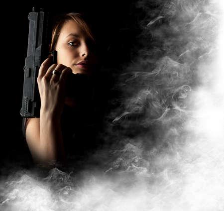 mujer con arma: Sexy chica sosteniendo la pistola de humo