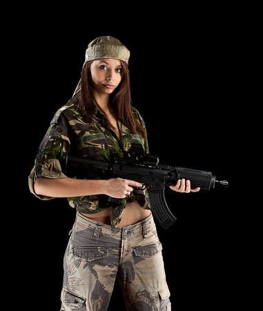 mujer con pistola: Militar del Ej�rcito chica Holding Gun fondo negro aislado Foto de archivo