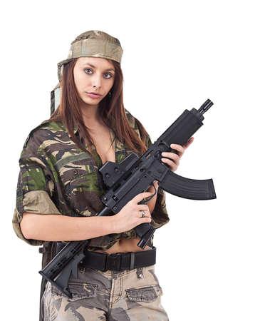 Disparo de mujer con uniforme militar que presenta contra el fondo blanco.