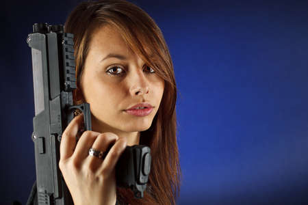 Young girl holding gun on blue background  photo