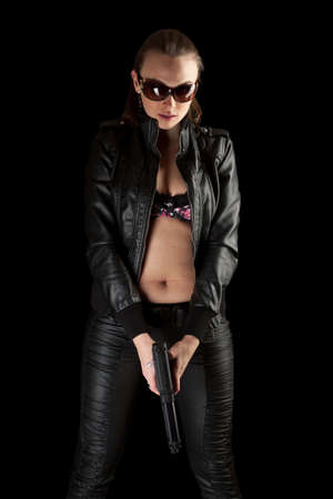 sexy police: Beautiful girl in black leather jacket and gun in her hands isolated on black background  Stock Photo