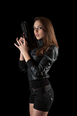 Shot of a sexy girl posing with guns isolated in black