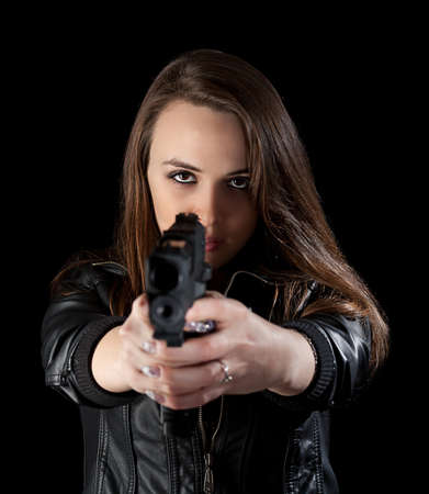 Shot of a beautiful girl holding gun, isolated on black background  photo