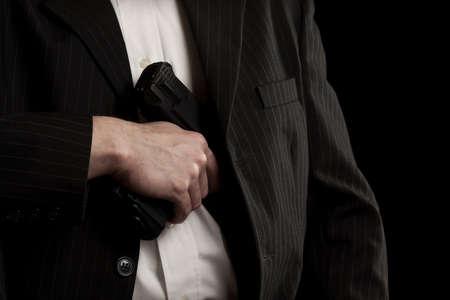 Man drawing his gun from coat pocket Stock Photo - 15348442
