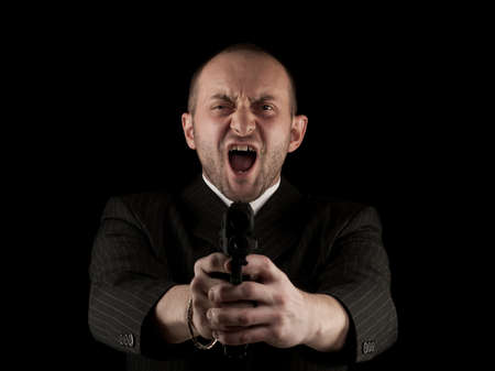 Angry Man Holding Gun and screaming, isolated on black photo