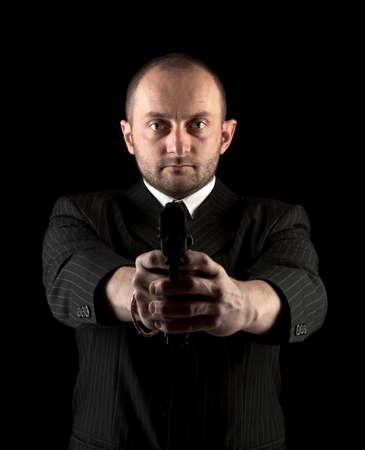 barrel pistol: Dangerous man in black suite with gun Stock Photo