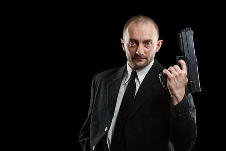 Businessman with a gun, isolated on black  photo