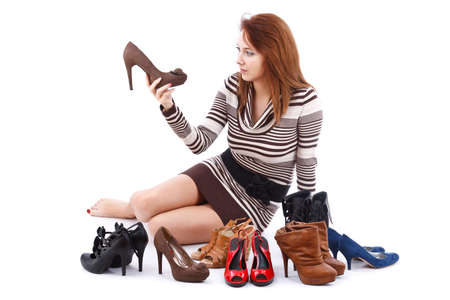 Junge Frau sitzt auf dem Boden von Schuhen umgeben Standard-Bild - 15388832
