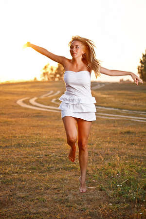 Beautiful young woman outdoor on the meadow on a summer day photo