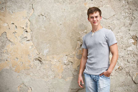 Young man posing outdoor in a grunge wall background photo