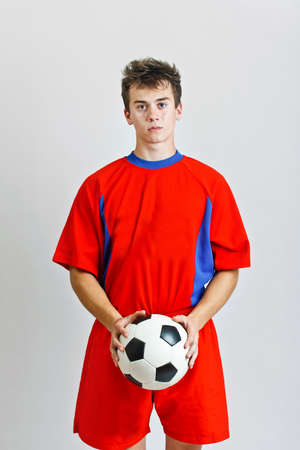 Soccer player is holding ball on gray background  photo