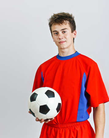 Young soccer player is holding ball on gray background  photo