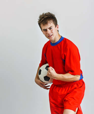 Young soccer player holding a ball against grey background photo