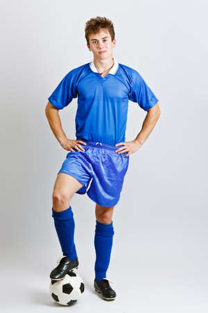 Soccer player with ball full length portrait, studio shot photo