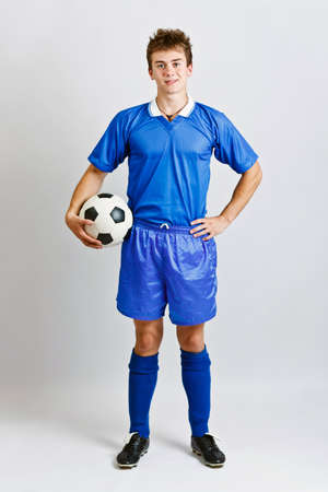 Soccer player with ball, studio shot photo