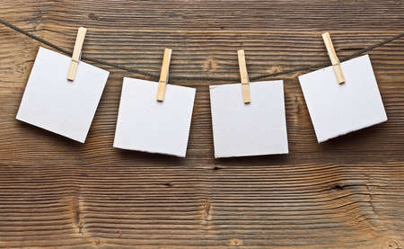 clothes line: Paper card and clothes peg on a wooden background Stock Photo